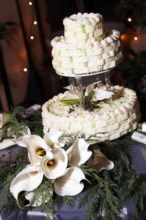 Wedding cake on a table with candles and white flowers, focus is on the cake top Stock Photo - 784077