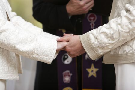 gay lifestyle: Two women holding hands during a wedding celebration Stock Photo