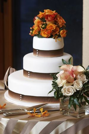 A fancy wedding cake, the focus is NOT on the cake, but on the flowers in the foreground.