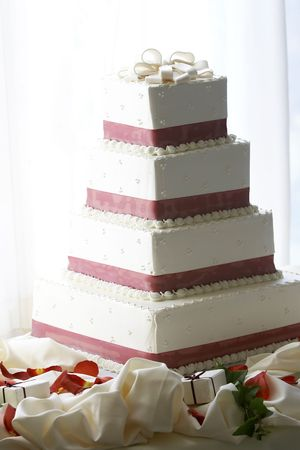 layer cake: A four tiered wedding cake, heavily backlit with blown out highlights Stock Photo