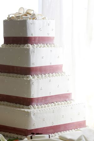 sidelit: A four tiered wedding cake, heavily sidelit with blown out highlights