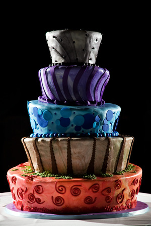 layer cake: This is a very cool cake from a wedding. its five tiered and full of color. It sits on a white table cloth with a black background. Cartoon style design. Stock Photo