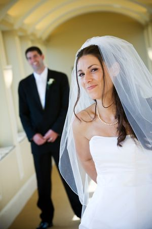 Bride and groom with the man standing in the background. Shallow depth of field, dark haired woman with a smile. Stock Photo