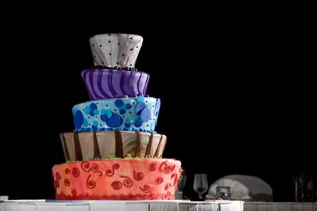cake background: This is a very cool cake from a wedding. it is five tiered and full of color. It sits on a white table cloth with a black background. Cartoon style design. Stock Photo