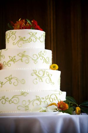 Wedding cake with four tiers, flowers, and swirl details