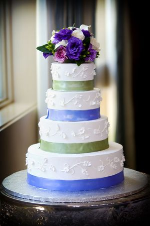 setting table: A large multi level wedding cake with purple flower topper