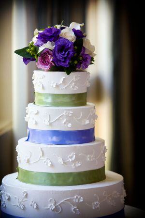 topper: A large multi level wedding cake with purple flower topper
