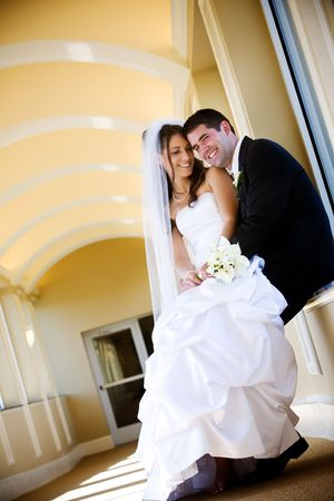 a bride and her groom, she is sitting in his lap and he is looking at the camera. A very sweet and attractive couple.