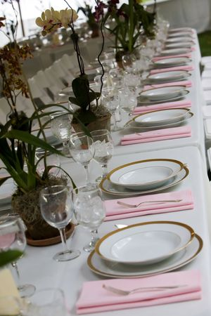 wedding table arranged with plates and glasses at a catered event