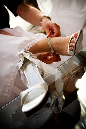 detail of a bride putting on her fancy high heels