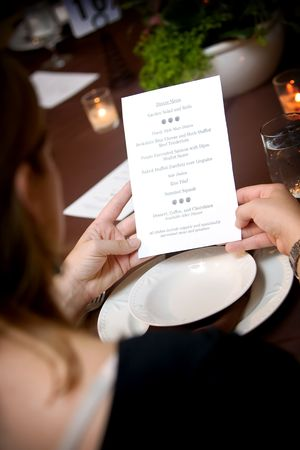 catered: a woman reading from an organic menu during a catered wedding event