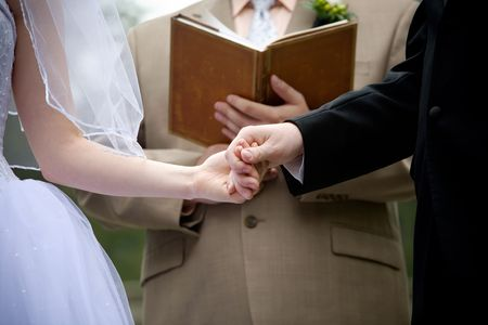 the bride and groom are holding hands during the wedding rings exchange