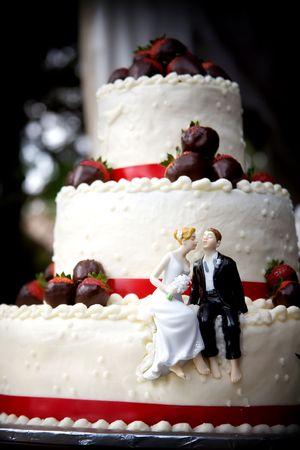 작은 신부와 신랑이 딸기 덮여 웨딩 케이크에 키스를 준비 앉아