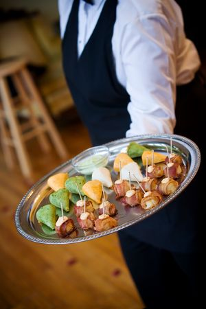 a waiter carries a platter of appetizers during a catered social event