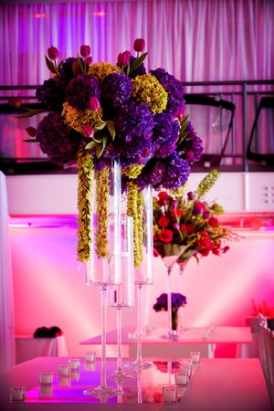 big and bold flower arrangements for the tables. Details from a wedding. - very colorful due to unique lighting