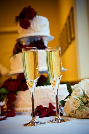 two glasses of champagne with a wedding cake in the background photo