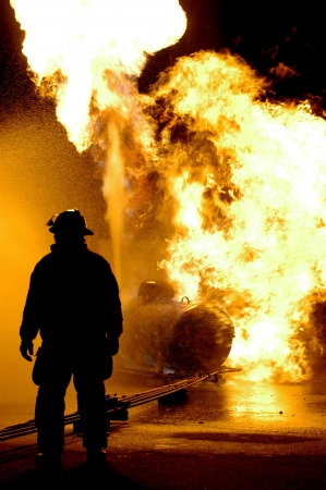 A fire fighter looks on as a propane tank burns.