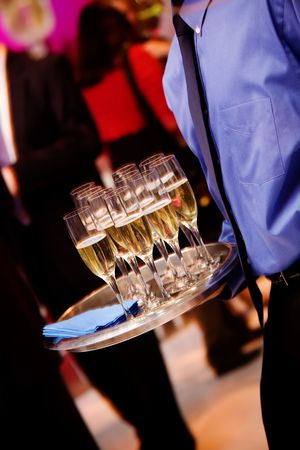champagne glasses being served by a waiter NOTE this photo has slight movement that helps to show the wait staff in action