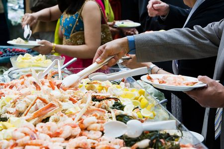 Photo of cooked shrimp and crab legs served at a wedding during cocktail hour. This image has a very shallow depth of field. Stock Photo