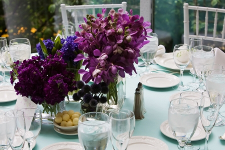 Beautiful purple bouquet of flowers on a table set for dinner