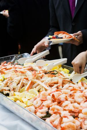 Photo of cooked shrimp and crab legs served at a wedding during cocktail hour. This image has a very shallow depth of field. photo