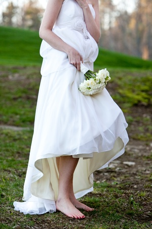 dirty feet: bride wearing no shoes in the mud Stock Photo