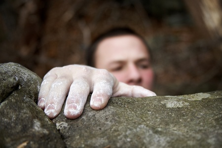 A climber reaches the top of a boulder. His visible hand is covered in white chalk, and his face is just peeking over the edge. photo