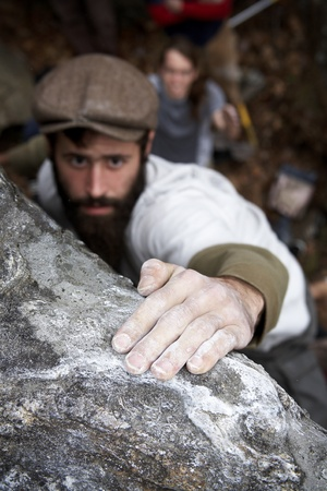 grabbing hand: A bearded man wearing a hat reaching the top of a boulder as his friend spots him in the background to help make sure he doesnt get hurt in case of a fall. Stock Photo