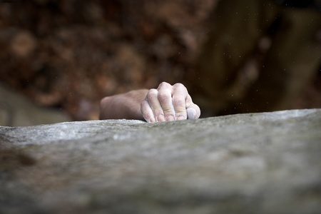 rock climb: Grabing onto a small handhold, a climber makes his way to the top. His hand is covered in chalk, and there is a very shallow depth of field. The white specks are small pieces of chalk dust flying through the air. Stock Photo