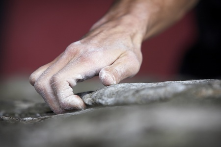 Grabing onto a small handhold, a climber makes his way to the top. His hand is covered in chalk, and there is a very shallow depth of field. photo
