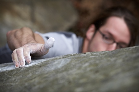 A man grasping onto a boulder in an attempt to reach the top of a hard climb. He is peaking over the rock looking for a new hand hold