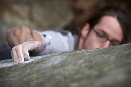 klimplant: Een man grijpen op een rotsblok in een poging om de top van een harde klim te bereiken. Hij is een piek boven de rots op zoek naar een nieuwe hand greep