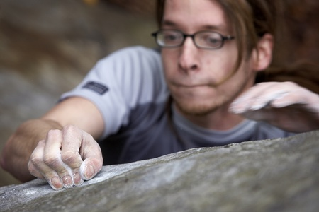 A man grasping onto a boulder in an atempt to reach the top of a hard climb. There is motion in one hand as he looks for a place to hold onto. photo