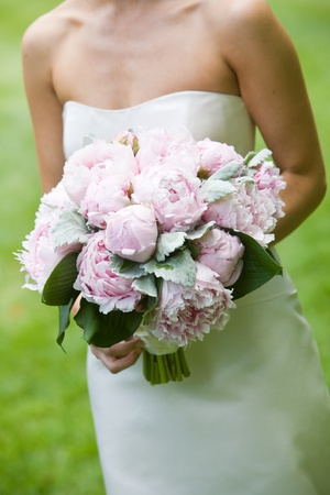 Bouquet of pink wedding flowers being held by a bride