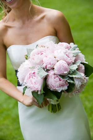 bridal bouquet: A wedding bouquet on pink flowers being held by a happy bride