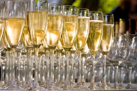 een rij van glazen gevuld met champagne zijn opgesteld klaar om te worden geserveerd Stockfoto