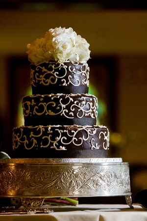 A chocolate wedding cake with white frosting details and flowers on top