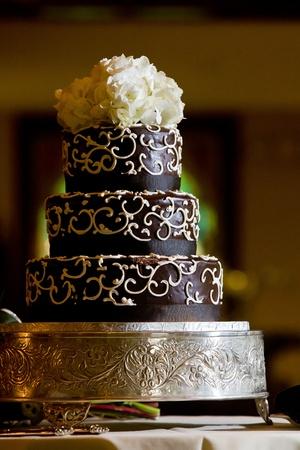 Een chocolade bruidstaart met wit glazuur details en bloemen op de top