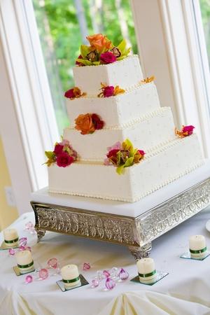 실버베이스에 여러 레이어와 꽃과 흰색 웨딩 케이크