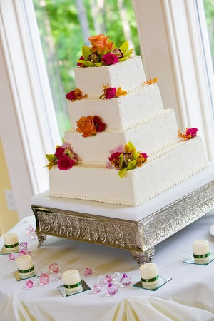 A white wedding cake with multiple layers and flowers on a silver base photo