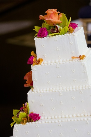 A white wedding cake with multiple layers and flowers. Wedding details.