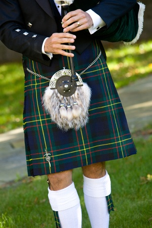 scot: Scottish bagpiper playing bagpipes. This is a detail shot of a man wearing a kilt