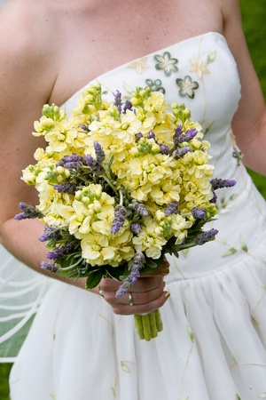 Bride holding her large wedding bouquet of flowers in yellow and purple photo