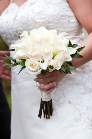 bridal wedding bouquet of flowers in white and green held by a bride photo