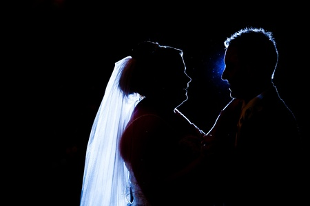 A bride and groom are having their first dance  silhouette of a couple dancing