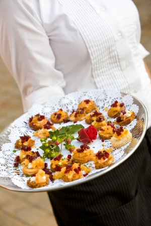 person appetizer: food being served by a waiter during a wedding or catered social event