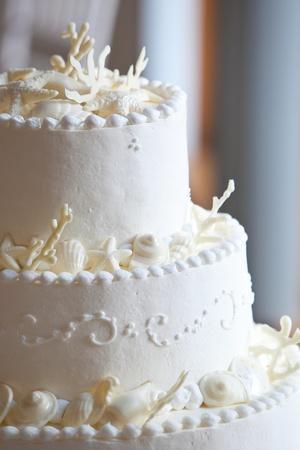 white ocean themed wedding cake with miniature seashell design and details Standard-Bild