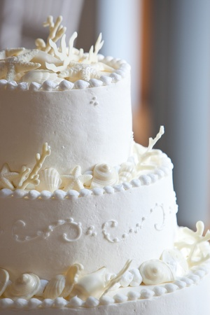 wedding reception: white ocean themed wedding cake with miniature seashell design and details Stock Photo