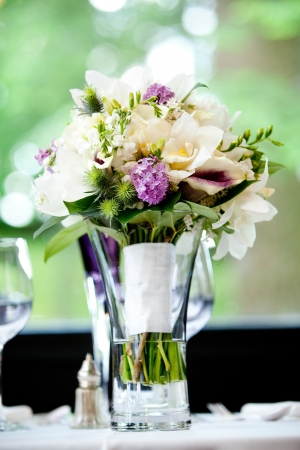 A brides wedding bouquet of flowers sitting in a vase full of water. Very shallow depth of field, focus on the purple flowers