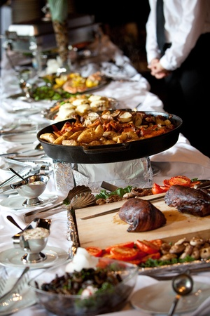 a buffet table with hot potatoes and a server in the background Фото со стока - 12959210